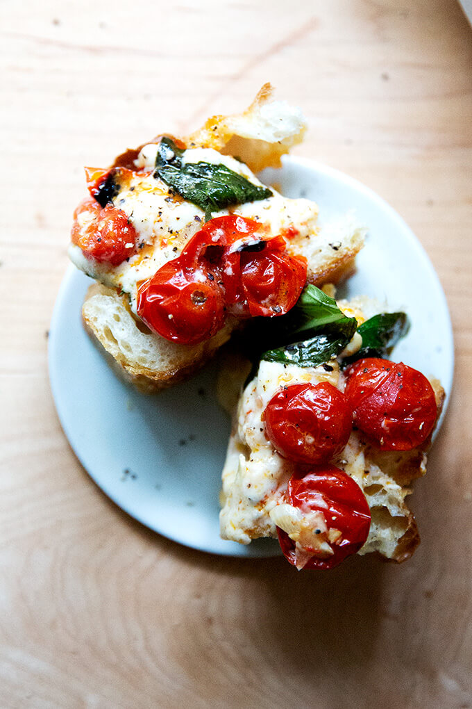A plate of two slices of focaccia topped with baked feta and tomatoes.