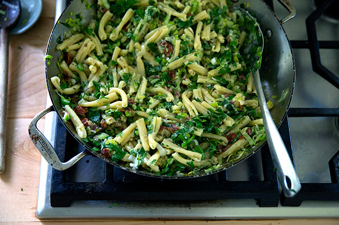 A skillet of pasta carbonara with leeks and lemon on the stovetop.
