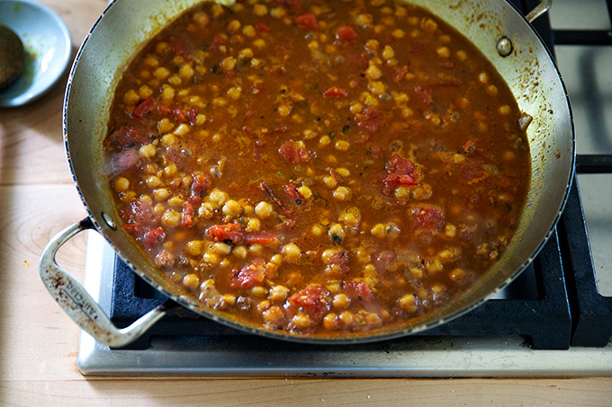 A skillet on the stovetop holding curry-spiced chickpeas and tomatoes.