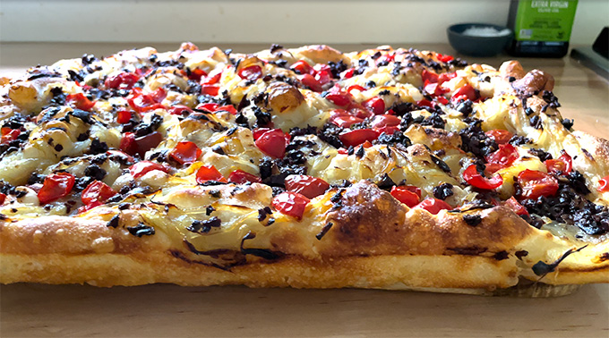 Baked pissaladière, side view, on a board.