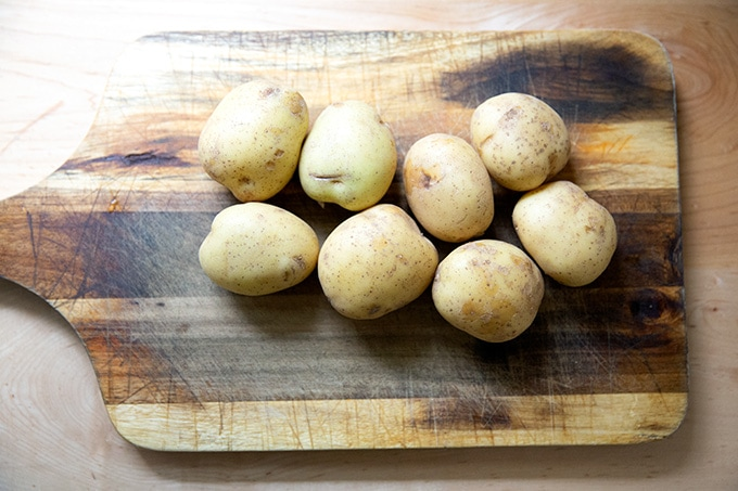 Yukon Gold potatoes on a cutting board.