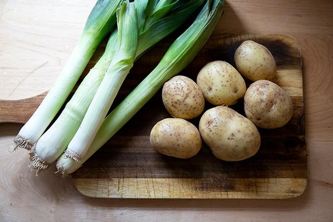 Leeks and potatoes on a board.