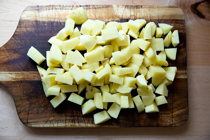 Peeled and diced Yukon Gold potatoes on a board.