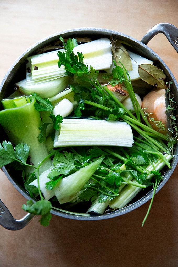 A soup pot holding vegetables to make vegetable stock.